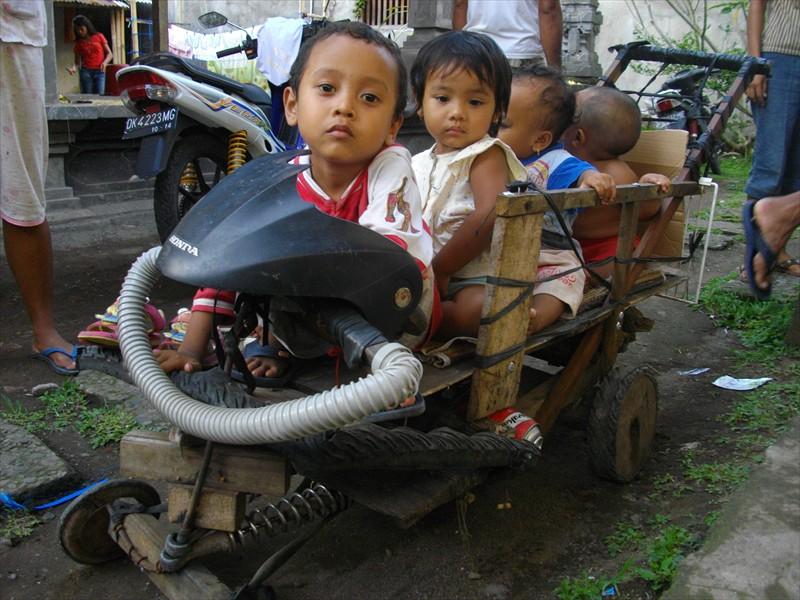 kinderen in Sidemen op een zelfgemaakt speelgoed vervoermiddel