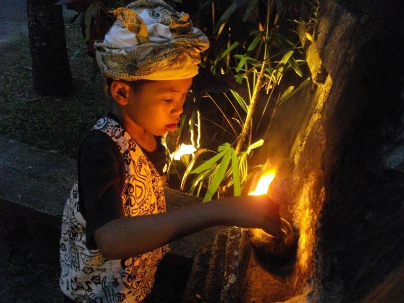 een Balinees kind dat een toorts ontsteekt tijdens een ceremonie in Umabian (Copy)